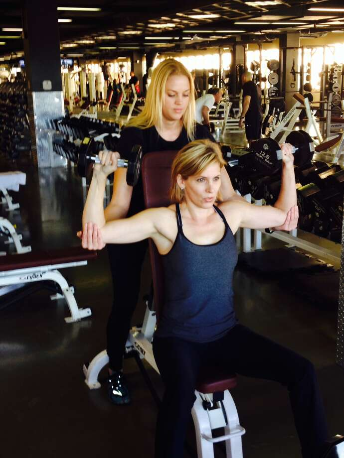 Houstonian Club certified personal trainer Jennifer Stevens guides client Allee Crosby through weight training and upper body strengthening workouts.