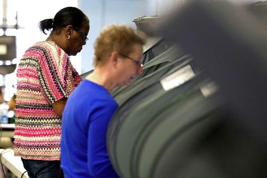 Joyce Eaton, left votes at Wainwright Elementary School on election day Tuesday, Nov. 5, 2013, in Houston. ( Johnny Hanson / Houston Chronicle ) Photo: Johnny Hanson, Staff / Houston Chronicle