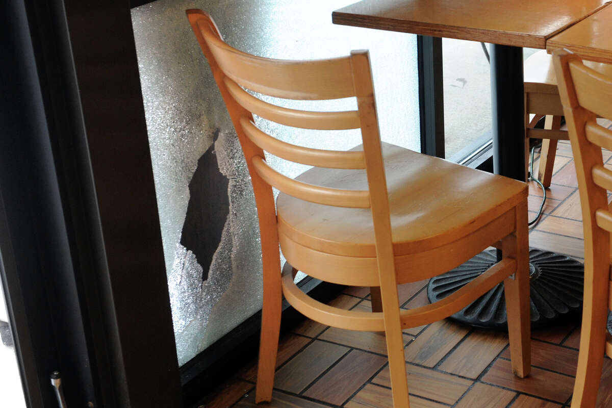 A bullet hole and shattered window next to the seat where Bridgeport Police Officer Juan Santiago accidently shot himself during breakfast at the Bagel King on upper Main St., in Bridgeport, Conn., Dec. 17, 2013.