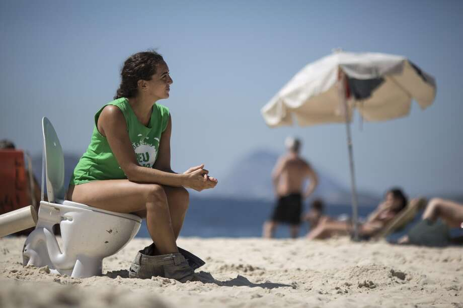 A woman sits on a toilet on Ipanema beach to protest water pollution in Rio de Janeiro, Brazil on Saturday, Jan. 25, 2014. The issue has gained increased attention since with just over two years to go before the start of the 2016 Olympic games, much of the metropolis' sewage flows untreated into the local waterways. (AP Photo/Felipe Dana, File) Photo: Felipe Dana, Associated Press