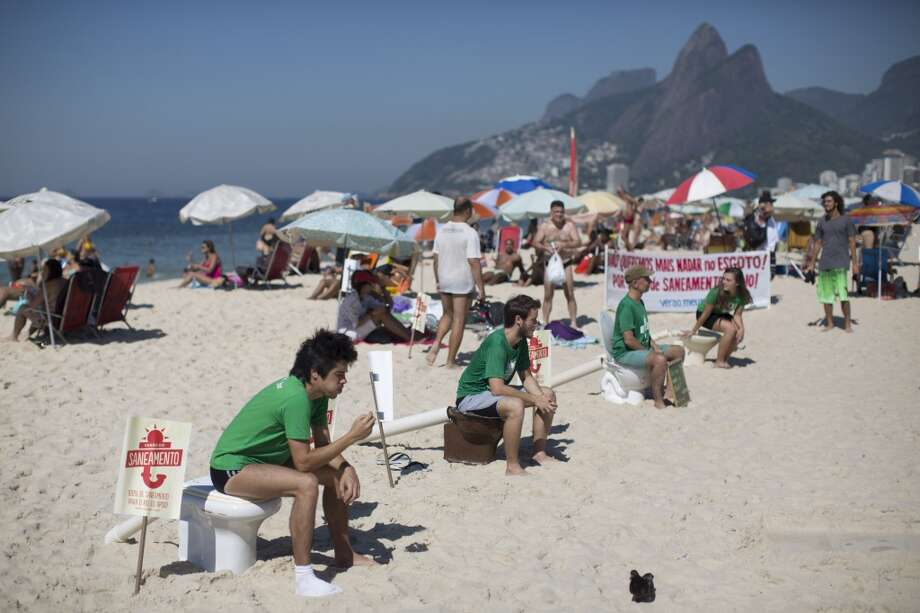 People sit on toilets on Ipanema beach to protest water pollution in Rio de Janeiro, Brazil, Saturday, Jan. 25, 2014. Water pollution has become a hot-button issue because much of the city's sewage flows untreated into the city's waterways and with just over two years to go before the start of the 2016 Olympic games. (AP Photo/Felipe Dana) Photo: Felipe Dana, Associated Press