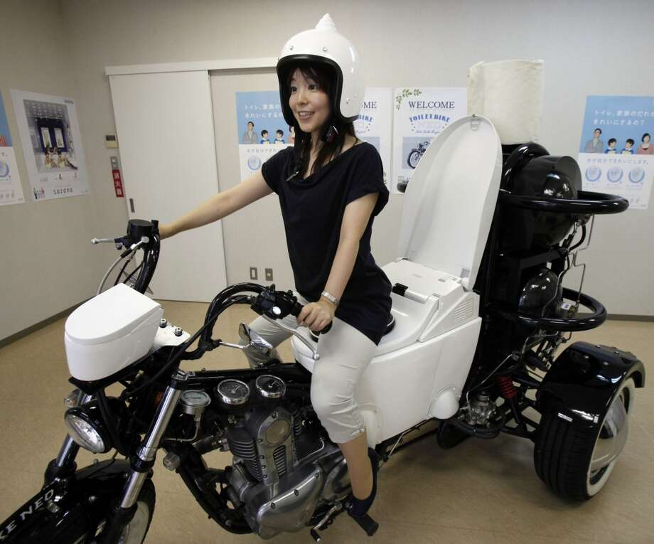 "Japanese toilet maker TOTO employee Akiko Matsuyama gets on a ""Toilet Bike Neo"" displayed at its showroom in Fujisawa, near Tokyo, Thursday, Aug. 23, 2012. TOTO rolled out the eco-friendly three-wheel 250cc motorcycle with a specially customized toilet-shaped seat that runs on bio-fuel from the discharge of livestock or waste water. (AP Photo/Koji Sasahara) Photo: Koji Sasahara, Associated Press"