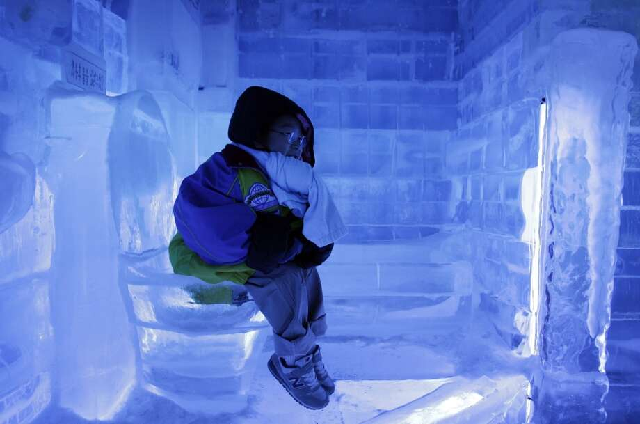 A South Korean boy sits on the ice toilet at Ice Gallery in Seoul, South Korea, Tuesday, Aug. 3, 2010. The sweltering heat continues for the recent several days in Seoul. (AP Photo/ Lee Jin-man) Photo: Lee Jin-man, AP