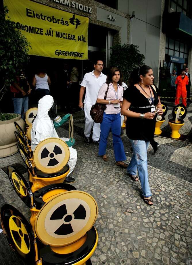 A Greenpeace activist demonstrates by sitting on one of several toilets installed at the entrance of the headquarters of the power company Eletrobras, as employees leave the building on March 23, 2008 in Rio de Janeiro's downtown. Greepeace protests against the Brazilian government's decision to build the nuclear power plant Angra 3 in Angra dos Reis, 270 km south of Rio de Janeiro. Photo: ANTONIO SCORZA, AFP/Getty Images