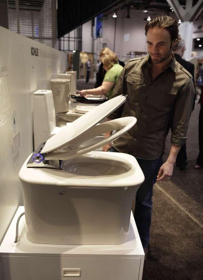 Matt Blashaw, a host for the DIY Network, tries out Kohler's Fountainhead toilet at the International Builders Show in Las Vegas, Thursday, Jan. 22, 2009. (AP Photo/Jae C. Hong) Photo: Jae C. Hong, AP