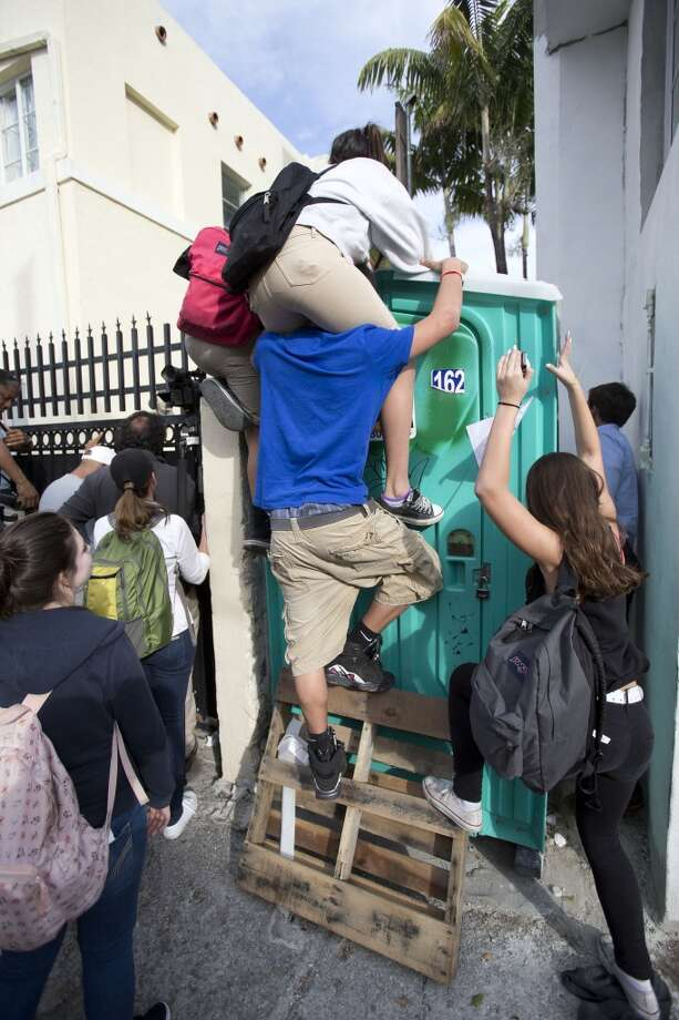 Young fans climb atop a portable toilet in hopes of gaining a glimpse of pop singer Justin Bieber, Friday, Jan. 24, 2014,  at a hotel where Bieber is said to be staying in Miami Beach, Fla. Bieber's arrest Thursday is another sign of the crazy lifestyle that has taken over the 19-year-old's image — but a more serious one given the gravity of his alleged offenses. Authorities say Bieber failed a field sobriety test early Thursday and he is facing driving under the influence charges after driving nearly twice the speed limit on a Miami Beach street. Police said he also resisted the arrest and smelled of alcohol. (AP Photo/Wilfredo Lee) Photo: Wilfredo Lee, Associated Press