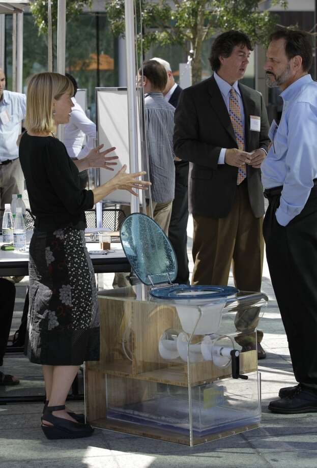 "Kara Nelson, left,  of the University of California at Berkeley, talks about the ""pHree Loo"" toliet, which is designed to safely disinfect sludge waste, as it sits on display at the ""Reinventing the Toliet"" Fair, Tuesday, Aug. 14, 2012, in Seattle, which is part of a Bill & Melinda Gates Foundation competition to reinvent the toilet for the 2.6 billion people around the world who don't have access to modern sanitation. (AP Photo/Ted S. Warren) Photo: Ted S. Warren, Associated Press"