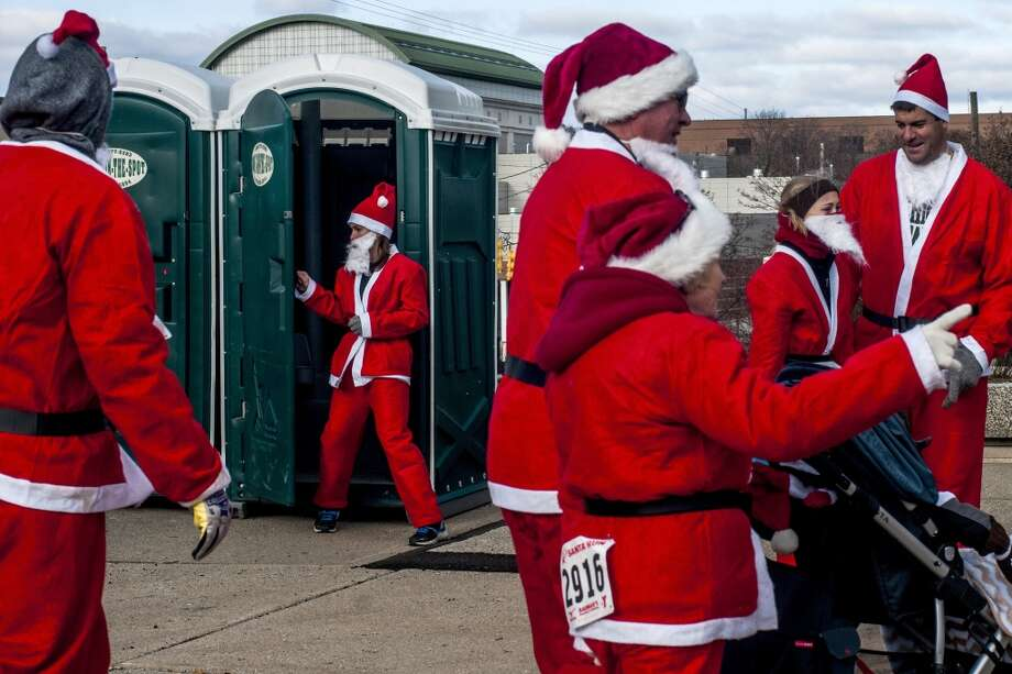 Whitley Huelskamp exits the portable toilet before running in the fourth annual Santa Run on Saturday, Dec. 7, 2013, Flint, Mich. (AP Photo/The Flint Journal, Jake May) LOCAL TV OUT; LOCAL INTERNET OUT Photo: Jake May, Associated Press