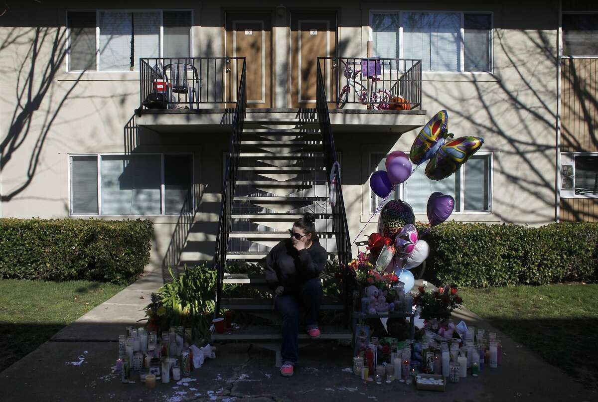 Savannah Fanjul thinks about her step-sister Kayleigh Slusher, Monday February 3, 2014, as she sits on the steps at the memorial outside the apartment building in Napa, Calif. Three year old Kayleigh Slusher was found dead, Saturday in her bed. The mother Sara Krueger and her boyfriend Ryan Scott Warner have been arrested on suspicion of murder and assault in connection with the killing of Kayleigh.