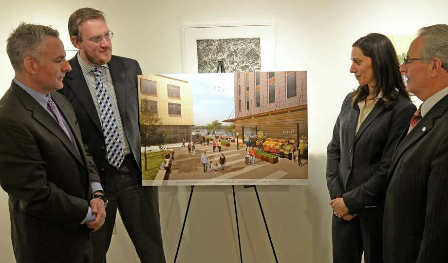 Gregory Burns, president Kirchhoff Consigli, left, Jeff Buell, second from left, Tina Mesiti Ceas from CSArch and Mayor Lou Rosamilia, right, look at an artist's rendering of the Monument Square development project Monday morning, Feb. 3, 2014, during a press conference in Troy, N.Y.       (Skip Dickstein / Times Union) Photo: SKIP DICKSTEIN / 00025595A