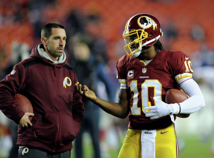 Washington Redskins offensive coordinator Kyle Shanahan, left, talks with quarterback Robert Griffin
