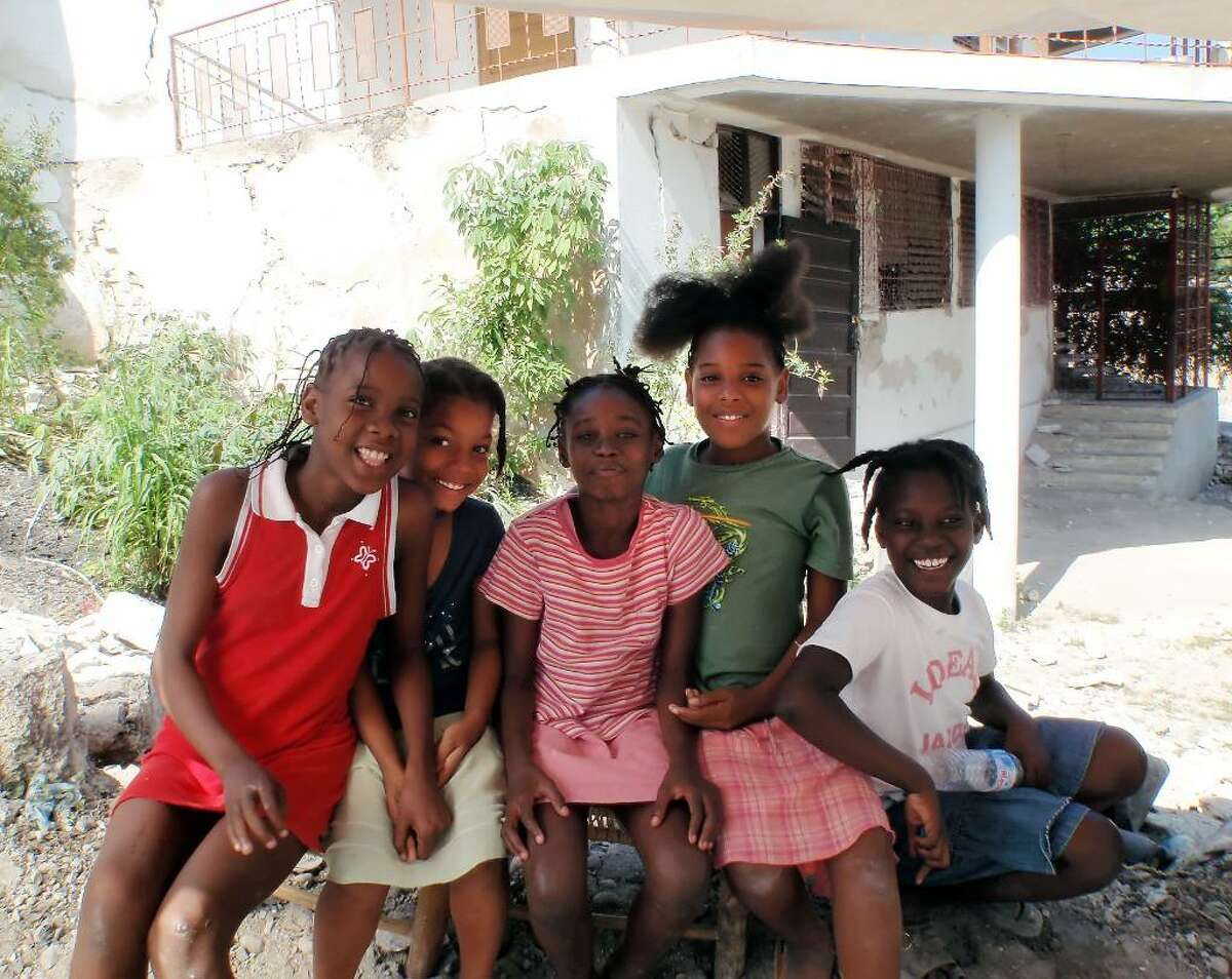 Children smile as they pose for a photo, survivors of the earthquake in Haiti, Jan. 2010.