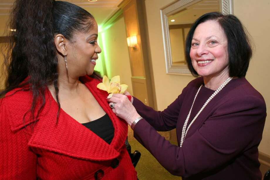 2010 Brava Award winner Deborah Williams gets a corsage pinned on her lapel by Adrianne C. Singer, President and CEO of the YWCA of Greenwich, before the start of Friday's award ceremony at the Hyatt Regency Greenwich. Photo: David Ames, David Ames/For Greenwich Time / Greenwich Time