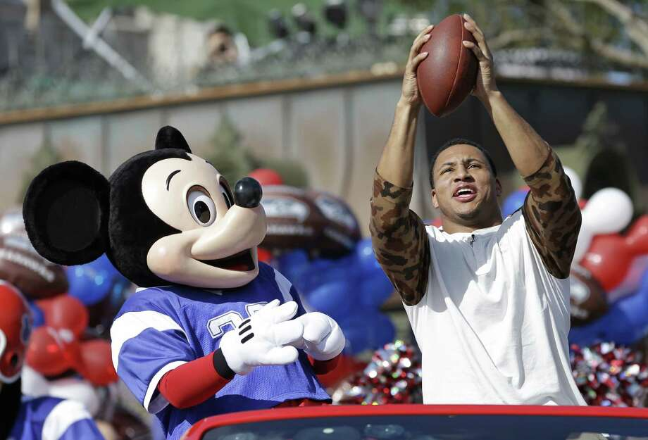 Super Bowl  MVP Malcolm Smith makes a catch while riding in a parade at Walt Disney World on Monday. Photo: John Raoux / Associated Press / AP