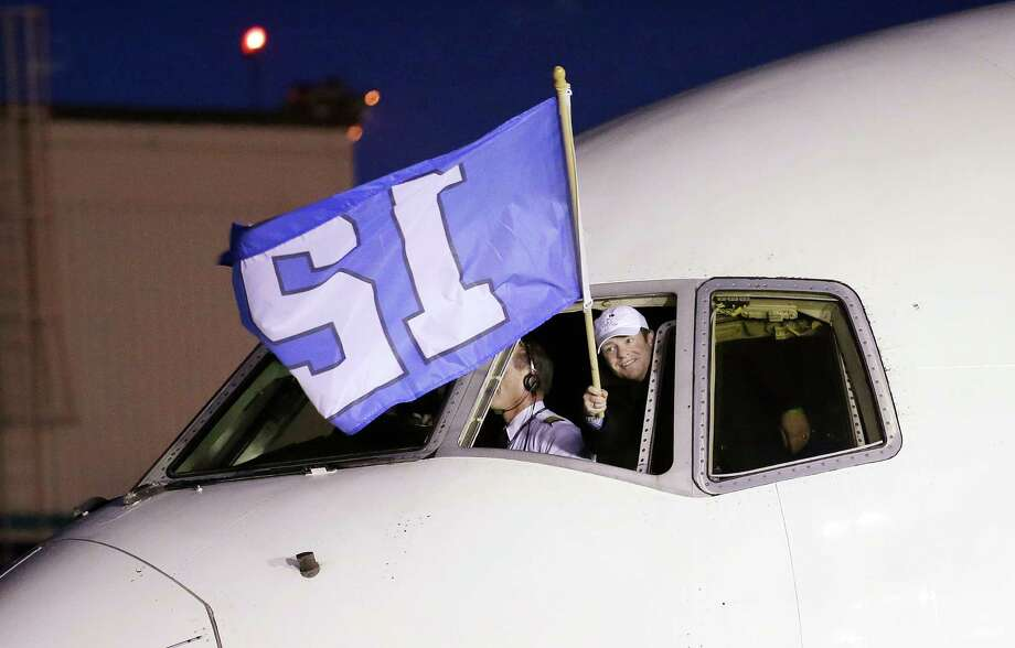 "Seattle Seahawks general manager John Schneider waves a ""12th Man"" flag out of the cockpit as the team arrival Monday, Feb. 3, 2014, at Seattle-Tacoma International Airport in Seattle. The Seahawks beat the Denver Broncos 43-8 in the Super Bowl on Sunday. (AP Photo/Elaine Thompson) Photo: Elaine Thompson, Elaine Thompson/AP / AP"