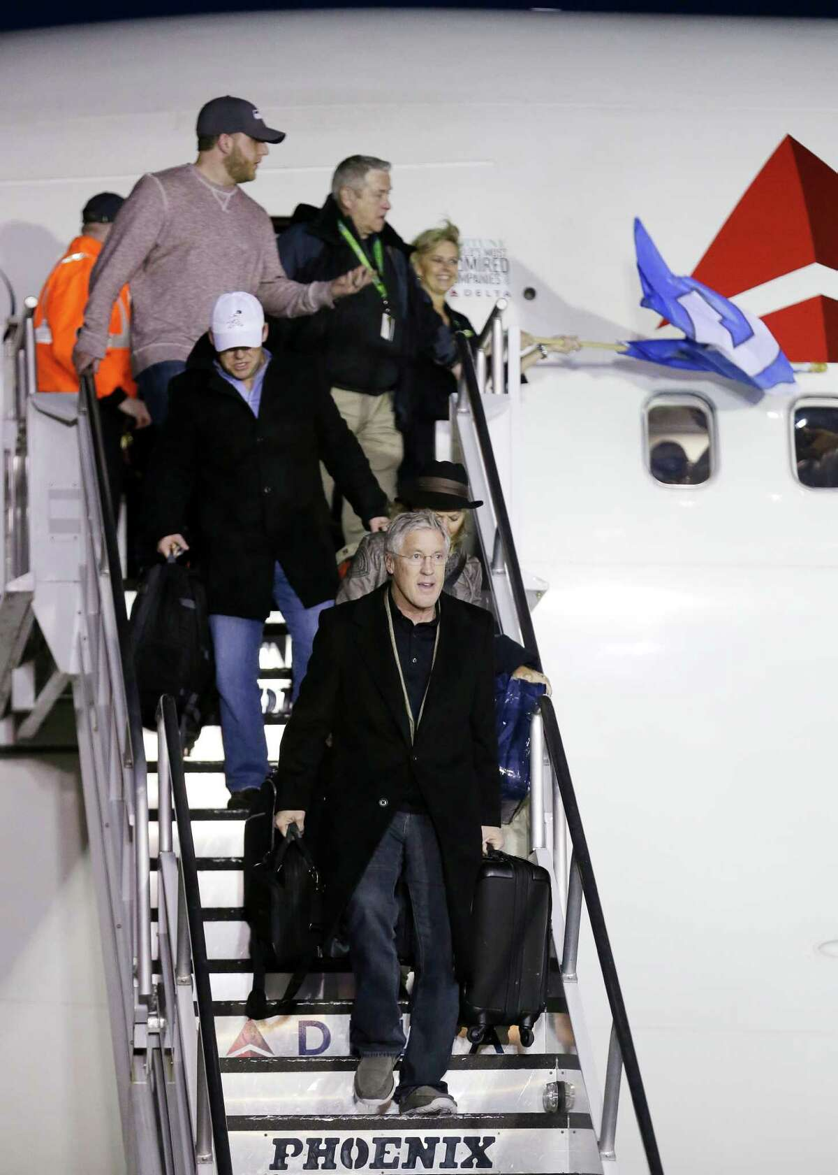 Seattle Seahawks head coach Pete Carroll, front, is followed by general manager John Schneider as he leads players and coaches off the plane upon the team's arrival Monday, Feb. 3, 2014, at Seattle-Tacoma International Airport in Seattle. The Seahawks beat the Denver Broncos 43-8 in the Super Bowl on Sunday. (AP Photo/Elaine Thompson)