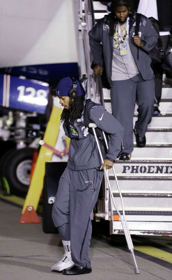 Seattle Seahawks' Richard Sherman walks on crutches on the team's arrival at Seattle-Tacoma International Airport, Monday, Feb. 3, 2014,  in Seattle. The Seahawks defeated the Denver Broncos 43-8 in the Super Bowl on Sunday. Photo: Elaine Thompson, AP / AP