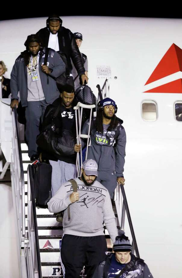 Seattle Seahawks' Richard Sherman, center right, carries crutches as he walks down stairs during the team's arrival at Seattle-Tacoma International Airport, Monday, Feb. 3, 2014, in Seattle. The Seahawks defeated the Denver Broncos 43-8 in the Super Bowl on Sunday. Photo: Elaine Thompson, AP / AP