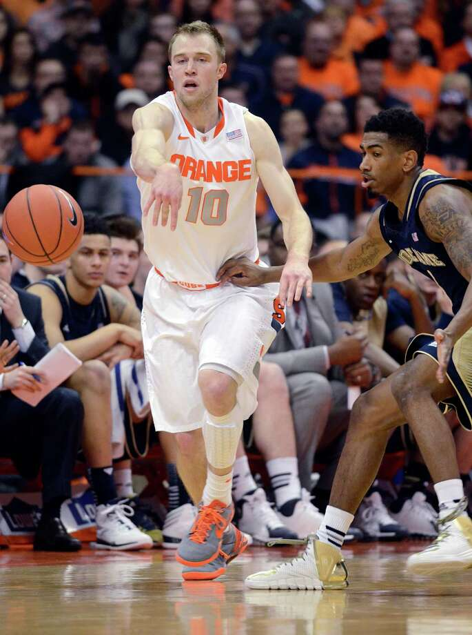 Syracuse's Trevor Cooney passes against Notre Dame's Eric Atkins during the first half of an NCAA college basketball game in Syracuse, N.Y., Monday, Feb. 3, 2014. (AP Photo/Kevin Rivoli) ORG XMIT: NYKR107 Photo: KEVIN RIVOLI / FR60349 AP