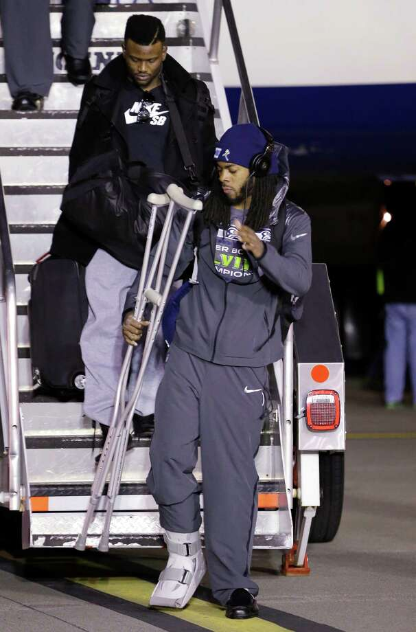 Seattle Seahawks' Richard Sherman carries crutches as he walks down stairs upon the team's arrival Monday, Feb. 3, 2014, at Seattle-Tacoma International Airport in Seattle. The Seahawks beat the Denver Broncos 43-8 in the Super Bowl on Sunday. Photo: Elaine Thompson, AP / AP