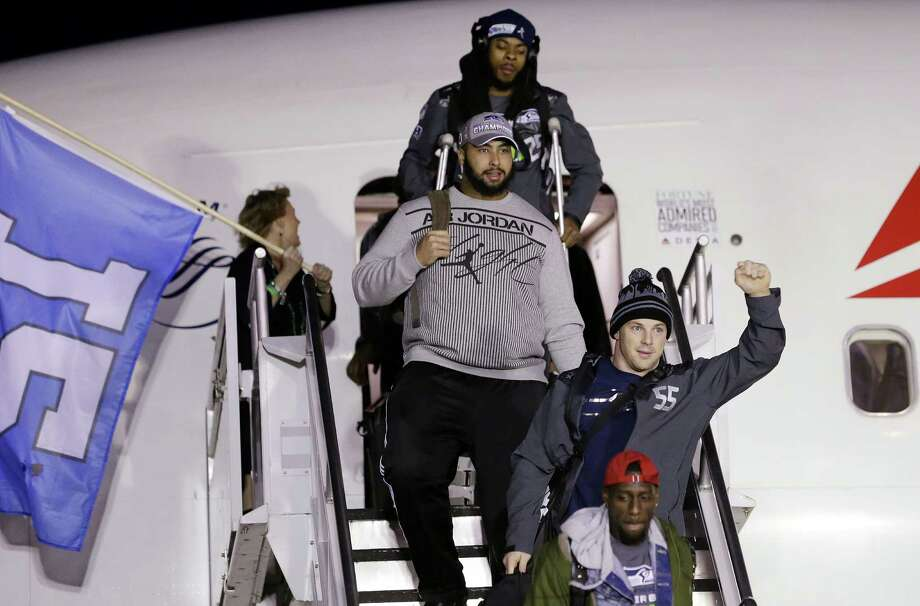 Seattle Seahawks' Heath Farwell, right, signals to fans on the team's arrival Monday, Feb. 3, 2014, at Seattle-Tacoma International Airport in Seattle. The Seahawks beat the Denver Broncos 43-8 in the Super Bowl on Sunday. Photo: Elaine Thompson, AP / AP
