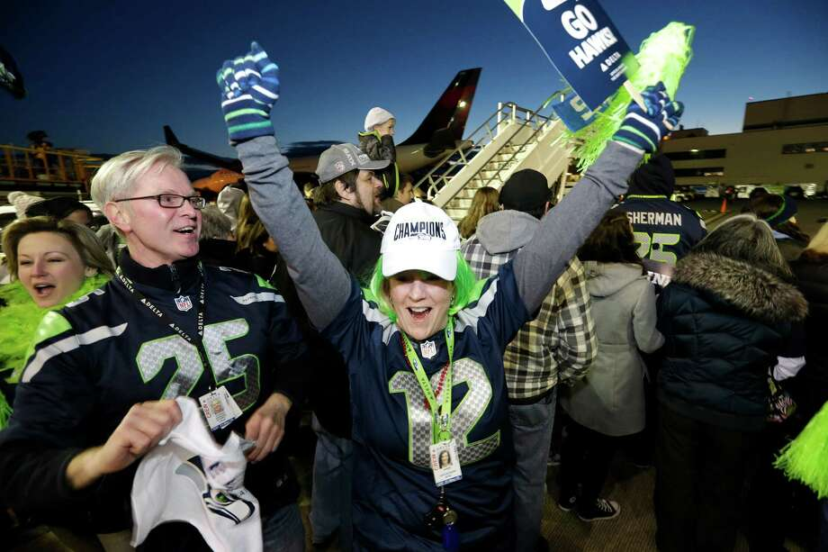 Fans start a cheer as they wait to greet Seattle Seahawks players and coaches on the team's arrival Monday, Feb. 3, 2014, at Seattle-Tacoma International Airport in Seattle. The Seahawks beat the Denver Broncos 43-8 in the Super Bowl on Sunday. Photo: Elaine Thompson, AP / AP