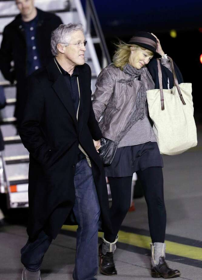 Seattle Seahawks coach Pete Carroll arrives with his wife, Glena, and the team Monday, Feb. 3, 2014, at Seattle-Tacoma International Airport in Seattle. The Seahawks beat the Denver Broncos 43-8 in the Super Bowl on Sunday. Photo: Elaine Thompson, AP / AP