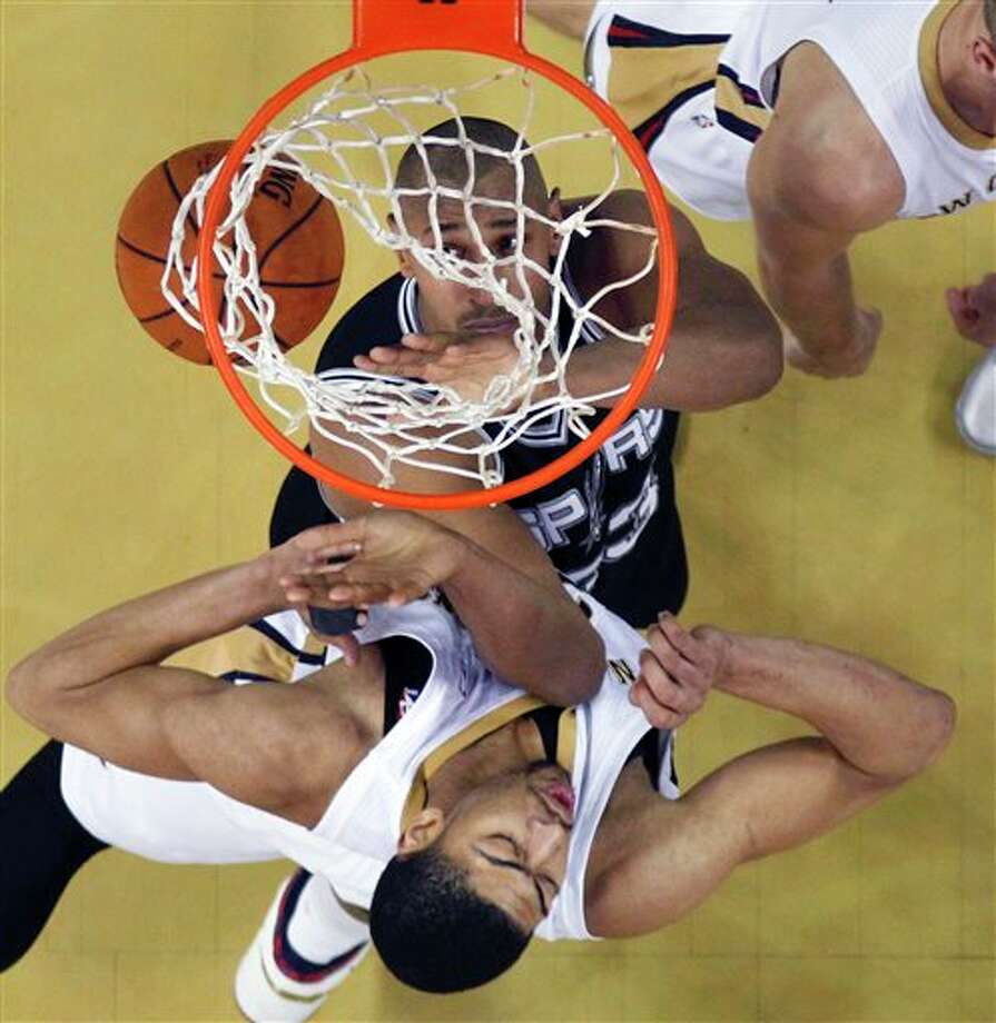 New Orleans Pelicans forward Anthony Davis, bottom, runs into San Antonio Spurs forward Boris Diaw (33) as he scores in the second half of an NBA basketball game in New Orleans, Monday, Feb. 3, 2014. The Spurs won 102-95. (AP Photo/Gerald Herbert) Photo: Gerald Herbert, AP / AP