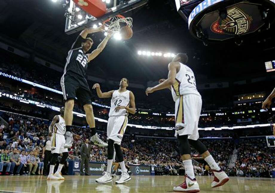 San Antonio Spurs center Tiago Splitter (22) slam dunks over New Orleans Pelicans center Alexis Ajinca (42) and Anthony Davis (23) in the first half of an NBA basketball game in New Orleans, Monday, Feb. 3, 2014. (AP Photo/Gerald Herbert) Photo: Gerald Herbert, AP / AP