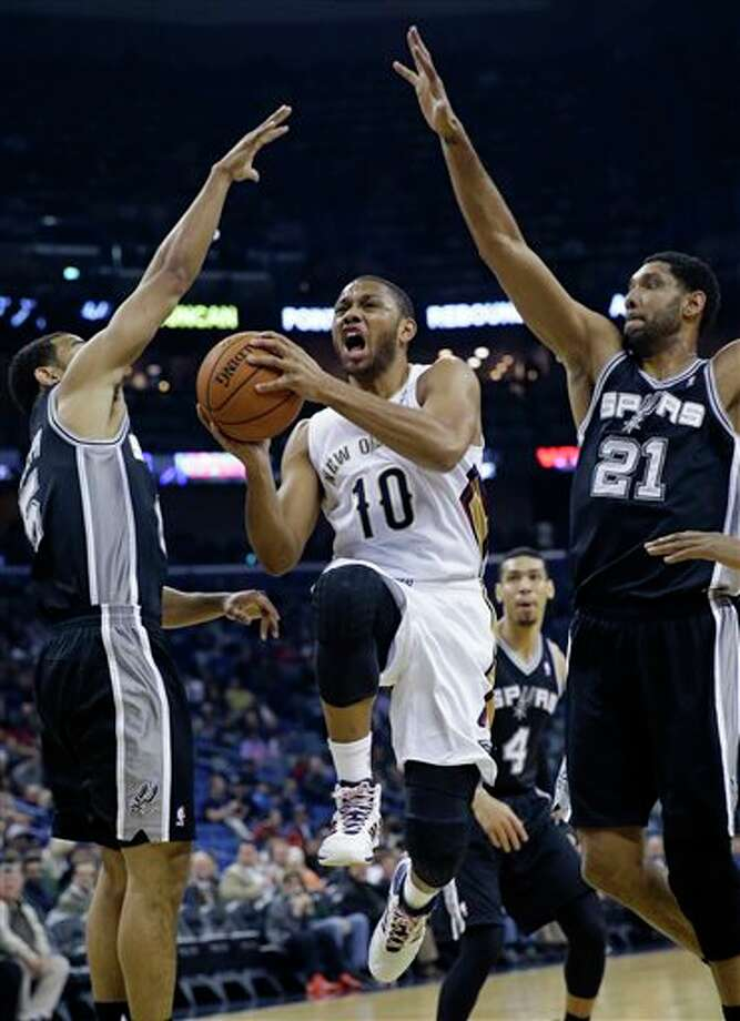 New Orleans Pelicans guard Eric Gordon (10) drives to the basket between San Antonio Spurs forward Tim Duncan (21) and Cory Joseph, left, in the first half of an NBA basketball game in New Orleans, Monday, Feb. 3, 2014. (AP Photo/Gerald Herbert) Photo: Gerald Herbert, AP / AP