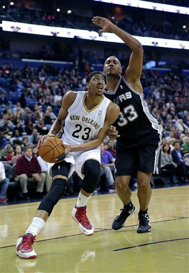 New Orleans Pelicans power forward Anthony Davis (23) drives to the basket against San Antonio Spurs power forward Boris Diaw (33) in the first half of an NBA basketball game in New Orleans, Monday, Feb. 3, 2014. (AP Photo/Gerald Herbert) Photo: Gerald Herbert, AP / AP