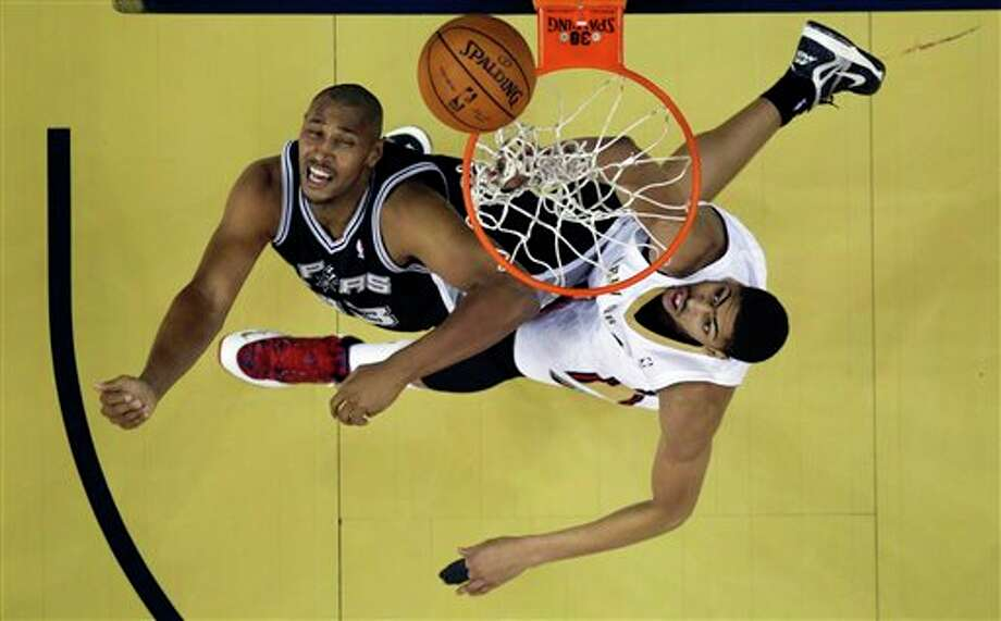 San Antonio Spurs forward Boris Diaw (33) goes to the basket against New Orleans Pelicans forward Anthony Davis, right, in the first half of an NBA basketball game in New Orleans, Monday, Feb. 3, 2014. (AP Photo/Gerald Herbert) Photo: Gerald Herbert, AP / AP