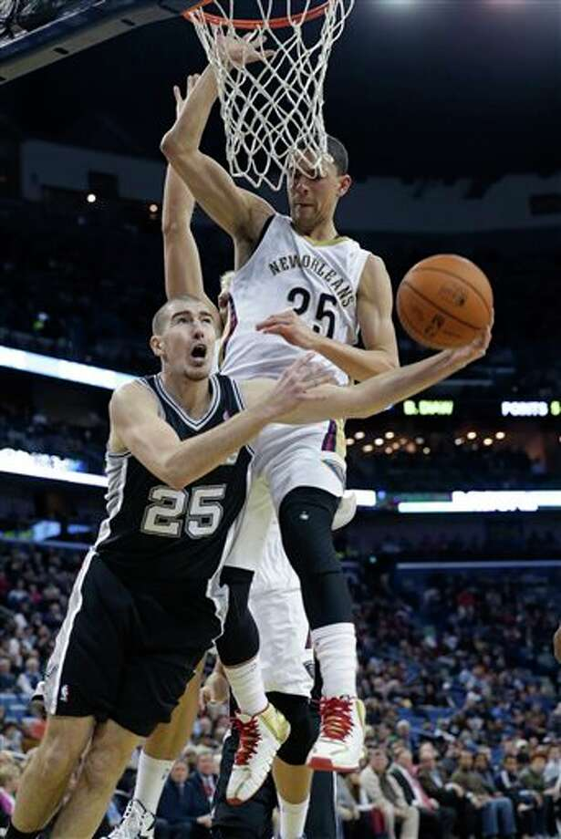 San Antonio Spurs guard Nando de Colo (25) drives to the basket against New Orleans Pelicans guard Austin Rivers (25), top, in the second half of an NBA basketball game in New Orleans, Monday, Feb. 3, 2014. The Spurs won 102-95. (AP Photo/Gerald Herbert) Photo: Gerald Herbert, AP / AP