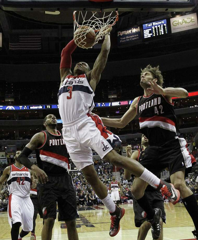 Wizards guard Bradley Beal dunks in front of the Trail Blazers' Robin Lopez (right) and LaMarcus Aldridge. Beal finished with 13 points and six assists. Photo: Alex Brandon / Associated Press / AP