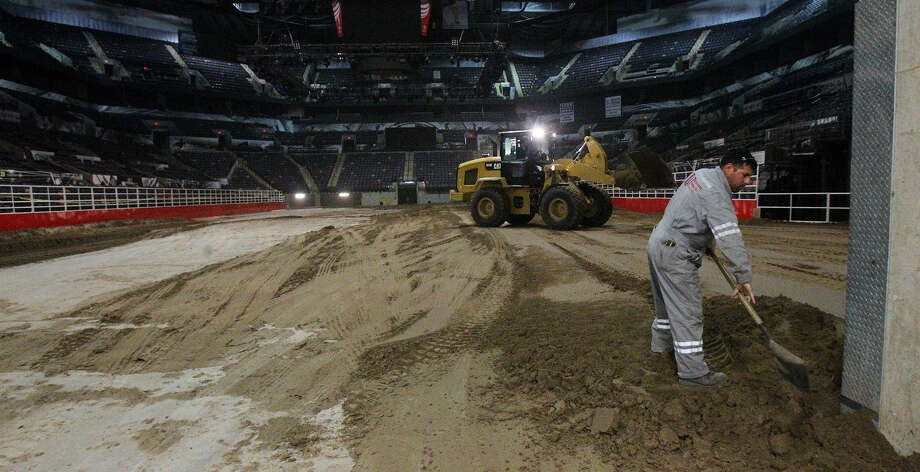 Miguel Ramirez, (right) an employee of Unison Drilling, spreads dirt Monday February 3, 2014 on the floor of the AT&T Center. The AT&T Center is undergoing the traditional conversion from the home of the Spurs to the home of the San Antonio Stock Show & Rodeo. The arena requires 2,160 tons of soil and takes 70 truckloads to move the soil from its storage location to the AT&T Center. Photo: JOHN DAVENPORT, SAN ANTONIO EXPRESS-NEWS / ©San Antonio Express-News/Photo may be sold to the public