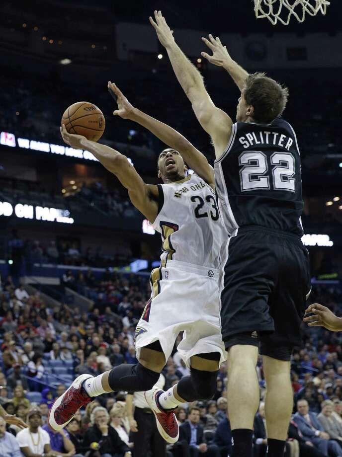 Anthony Davis (17 points, 16 boards) drives as Tiago Splitter defends. Photo: Gerald Herbert / Associated Press / AP