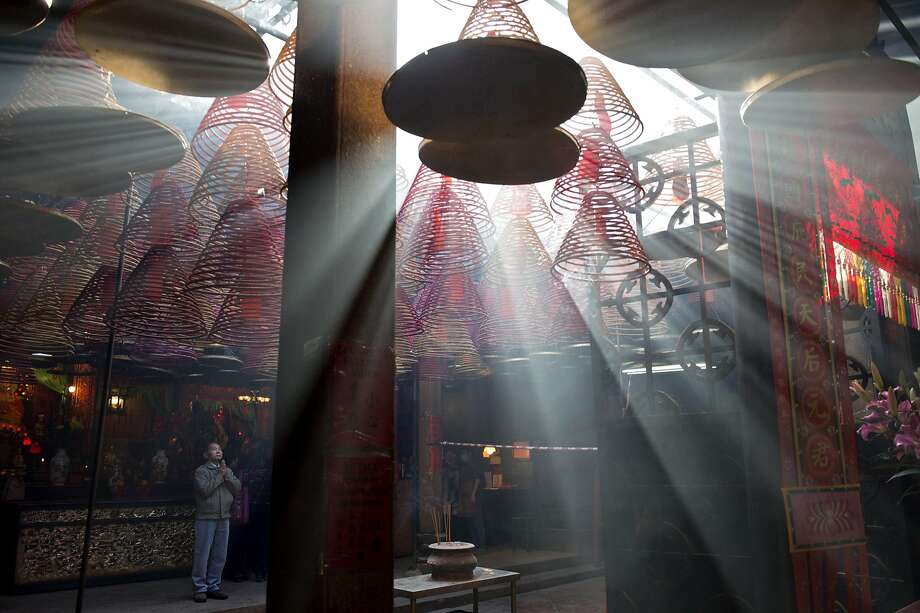 A man (L) prays as sunlight shines through hanging incense coils at the Tin Hau Temple in the Yau Ma Tei area of Hong Kong on the fourth day of the Lunar New Year holiday on February 3, 2014.  Chinese communities across Asia came together to usher in the Year of the Horse, with tens of thousands of worshippers flocking to temples across China to pray for good fortune in the new year.  TOPSHOTS  AFP PHOTO / Alex OgleAlex Ogle/AFP/Getty Images Photo: Alex Ogle, AFP/Getty Images