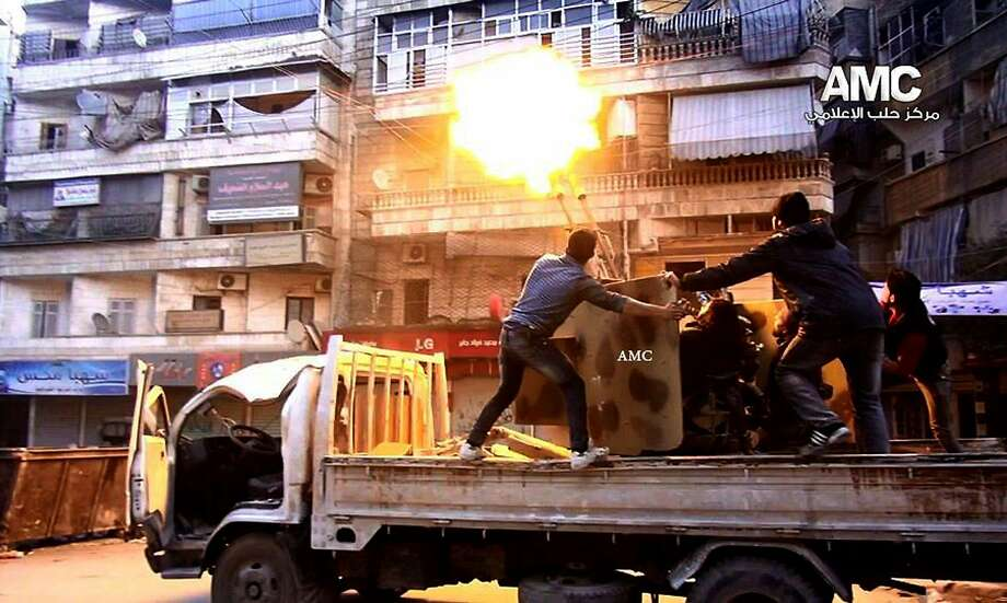 In this Saturday Feb. 1, 2014, photo provided by the anti-government activist group Aleppo Media Center (AMC), which has been authenticated based on its contents and other AP reporting, Syrian rebels fire their anti-aircraft gun at Syrian forces airplanes in Aleppo, Syria. Syrian government helicopters and warplanes unleashed a wave of airstrikes on more than a dozen opposition-held neighborhoods in the northern city of Aleppo on Sunday, in a ferocious attack that killed at least 36 people, including 17 children, activists said. The AMC logo has been inserted in top right corner and the initials AMC appear on weapon. (AP Photo/Aleppo Media Center, AMC) Photo: Hoep, Associated Press