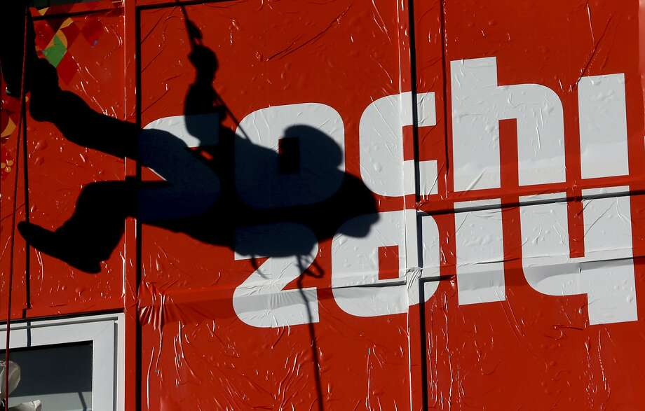 A worker climbs past an Olympic logo at the ski jumping venue during preparations for the 2014 Winter Olympics, Monday, Feb. 3, 2014, in Krasnaya Polyana, Russia. (AP Photo/Dmitry Lovetsky) Photo: Dmitry Lovetsky, Associated Press
