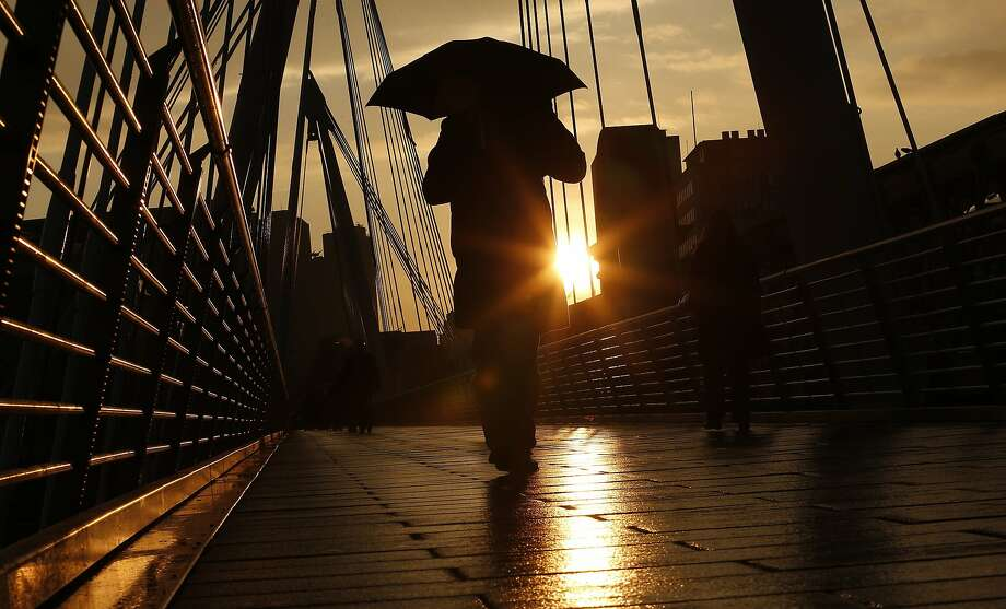 REFILE - CORRECTING NAME OF BRIDGE A pedestrian carries an umbrella as he walks over one of the Golden Jubilee Bridges in London January 31, 2014. REUTERS/Suzanne Plunkett (BRITAIN - Tags: SOCIETY TPX IMAGES OF THE DAY) Photo: Suzanne Plunkett, Reuters