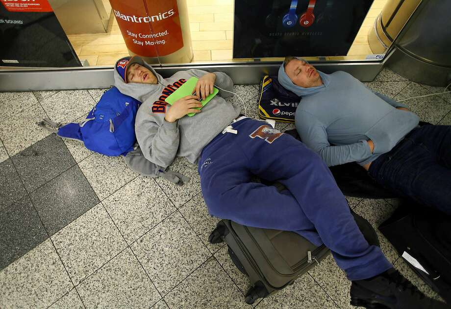 Denver Broncos fans Drew Brown (L) and Matt Robbins sleep in terminal C at LaGuardia Airport after their flights were delayed due to snowy weather in the Queens borough of New York February 3, 2014. REUTERS/Joshua Lott (UNITED STATES - Tags: ENVIRONMENT SOCIETY) Photo: Joshua Lott, Reuters