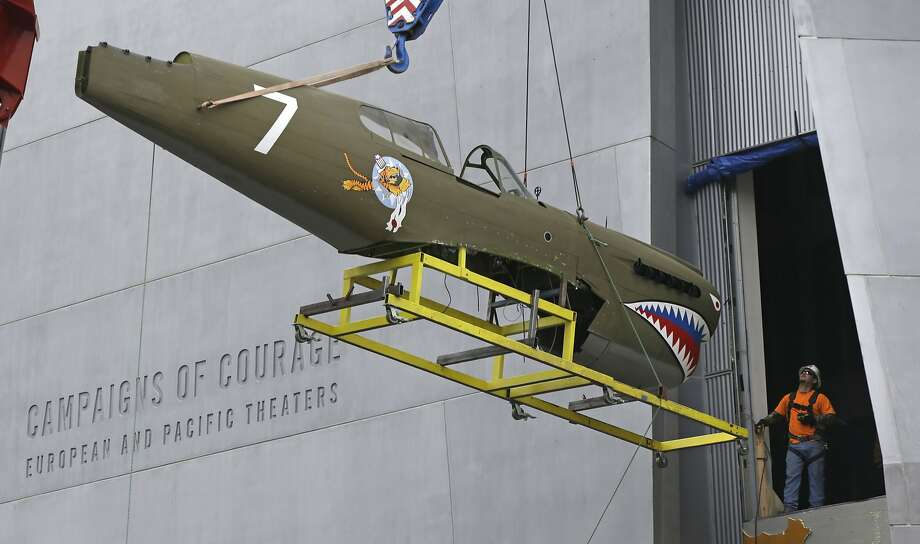 A restored P-40 Curtiss Warhawk fighter plane, one of only 32 known remaining in the world, is hoisted by crane to the second floor for permanent display at the National World War II Museum in New Orleans, Monday, Feb. 3, 2014. The plane, painted in the scheme of the famed Flying Tigers, will be displayed in the museum's new pavilion, Campaigns of Courage: European and Pacific Theaters. (AP Photo/Gerald Herbert) Photo: Gerald Herbert, Associated Press