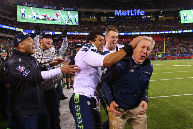 Seattle Seahawks quarterback Russell Wilson celebrates with coach Pete Carroll after Carroll was hit with Gatorade in the final minutes during the Super Bowl on Sunday, February 2, 2014 at MetLife Stadium in New Jersey. The Seahawks dominated the Denver Broncos 43-8. Photo: JOSHUA TRUJILLO, SEATTLEPI.COM / SEATTLEPI.COM