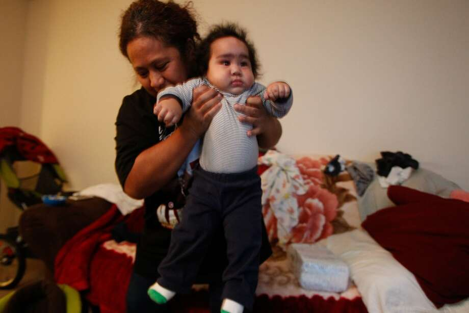 Sosefina Tagalu moves her son, Sammisano Otuhiva,  at their home in Daly City, Calif., on Thursday, Jan. 30, 2014. Otuhiva was 16 lbs. 1.74 oz. at birth and was 23 lbs. when last weighed in Dec. Photo: Mathew Sumner, Special To The Chronicle