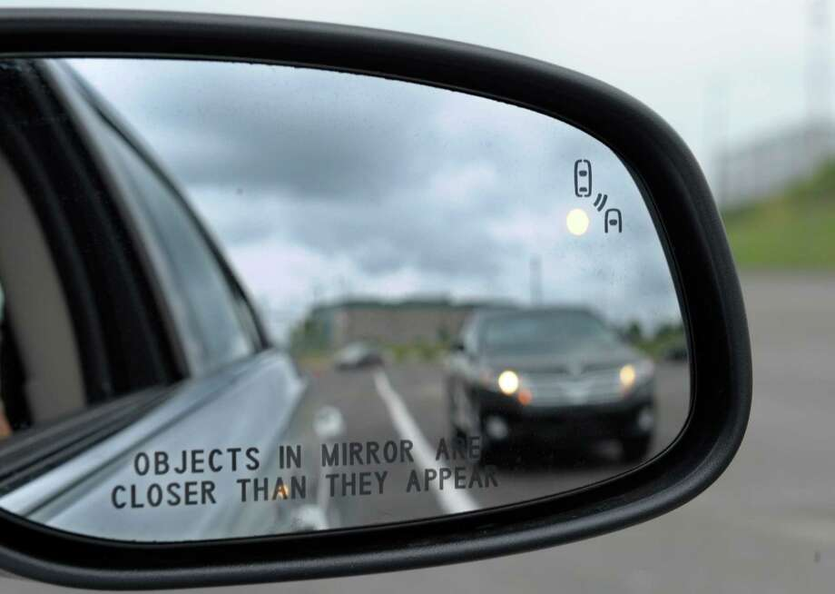 FILE - This May 22, 2012 file photo shows a side mirror warning signal in a Ford Taurus at an automobile testing area in Oxon Hill, Md. Federal officials are planning to announce Monday whether automakers should be required to equip new cars and light trucks with technology that enables vehicles to communicate with each other to prevent collisions. Such vehicle-to-vehicle communication could eventually transform traffic safety. Photo: Susan Walsh, AP / AP