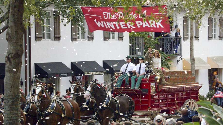 In this undated photo provided by Anheuser-Busch, Lt. Chuck Nadd and his girlfriend Shannon Cantwell wave as they ride aboard the famously-red Budweiser beer wagon pulled by Clydesdales in a parade, led by a marching band in Winter Park, Fla. The brewer fashioned the ad around the parade that ran during the Super Bowl.(AP Photo/Anheuser-Busch, Hand Out) Photo: Associated Press