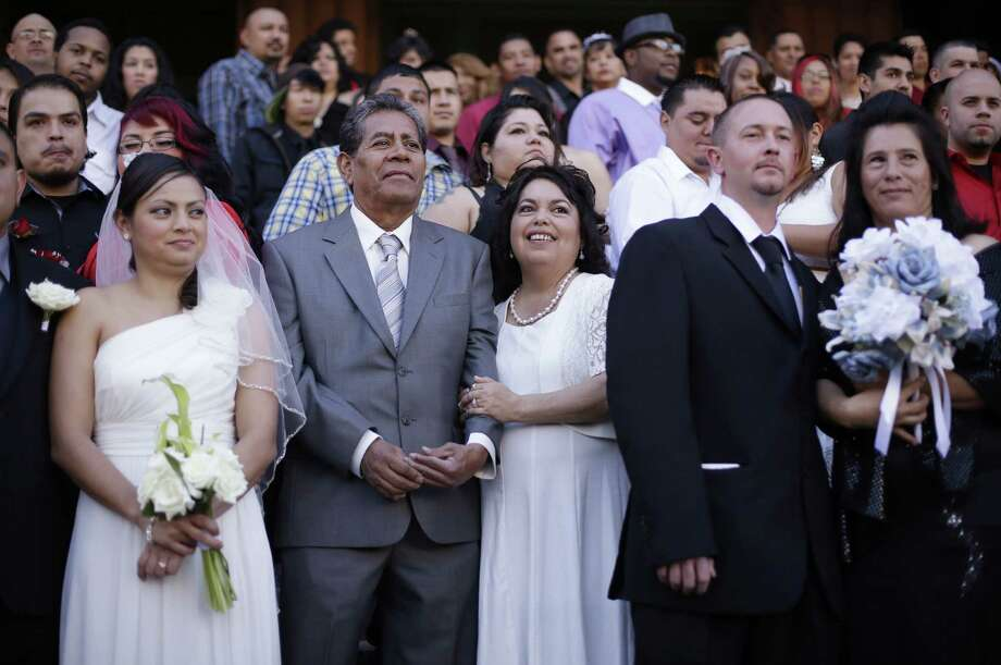 Dozens of couples take part in a group wedding on the steps of the Bexar County Courthouse last Valentine's Day.  The Rev. Joe Sullivan will be back this year to perform weddings for free beginning at 12:01 a.m. Feb. 14. Photo: Associated Press File Photo / AP