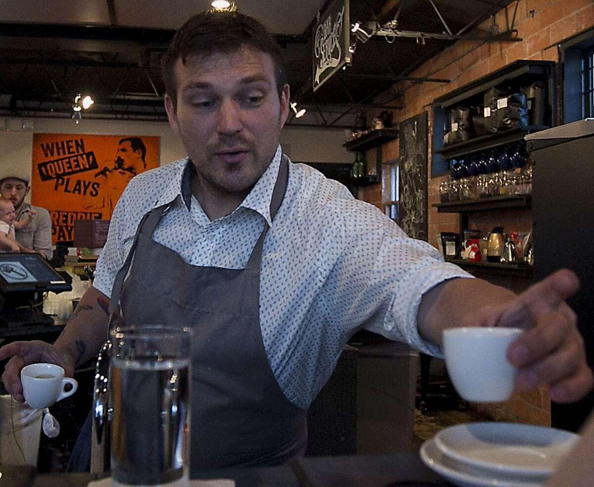 Owner David Buehrer serves a customer at Blacksmith coffee shop.