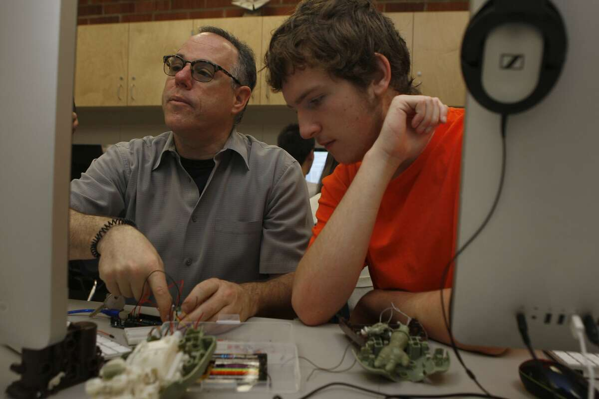 Teacher Glenn Corey (left) and student Calun Bliss work on a project in Corey's lab at Novato High School.