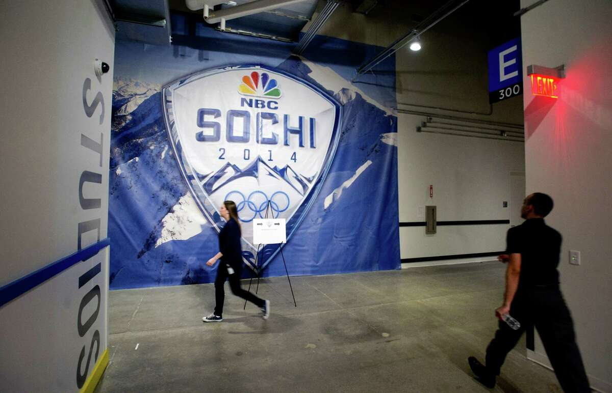 NBC Sports employees walk through halls decorated for the Sochi Olympics in Stamford, Conn., on Tuesday, February 4, 2014.